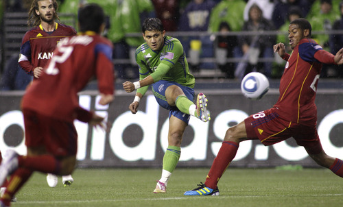Seattle Sounders' Fredy Montero, center, strikes the ball as Real Salt Lake's Chris Schuler, right, defends in the first half of an MLS playoff soccer match, Wednesday, Nov. 2, 2011, in Seattle. (AP Photo/Ted S. Warren)