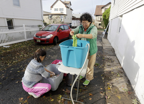 Yoriko Maio, left, and Kijung Takii wash clothes in the driveway of their home, which was flooded and is without power, in the wake of superstorm Sandy on Thursday, Nov. 1, 2012, in Little Ferry, N.J.  New Jersey residents across the state were urged to conserve water. At least 1.7 million customers remained without electricity.  (AP Photo/Mike Groll)(AP Photo/Mike Groll)