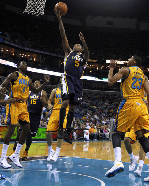 Utah Jazz point guard Mo Williams (5) scores past New Orleans Hornets power forward Anthony Davis (23) and small forward Al-Farouq Aminu (0) during the first half of an NBA basketball game in New Orleans, Friday, Nov. 2, 2012. The Hornets won 88-86. (AP Photo/Jonathan Bachman)