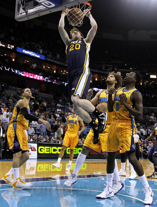 Utah Jazz shooting guard Gordon Hayward (20) dunks the ball over New Orleans Hornets shooting guard Austin Rivers, left, and small forward Al-Farouq Aminu (0) during the first half of an NBA basketball game in New Orleans, Friday, Nov. 2, 2012. (AP Photo/Jonathan Bachman)