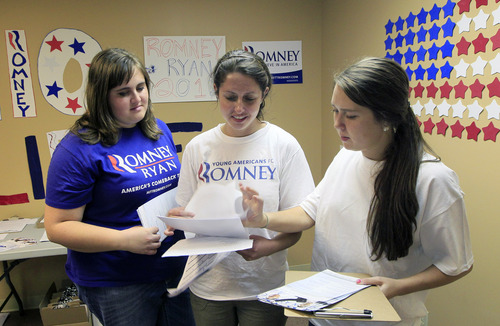 This photo taken Oct. 2, 2012 shows volunteers, from left, Kristin Turner, Beth Hamad, and Leslie Reynolds, go over a list of potential voters at a Republican campaign office in Cincinnati. Some campaign workers in the battleground state of Ohio have a particularly challenging mission - find votes in opposition territory.  (AP Photo/Al Behrman)