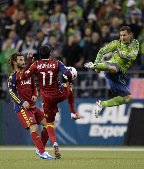 Seattle Sounders' Christian Tiffert, right, leaps as he battles with Real Salt Lake's Javier Morales (11) and Kyle Beckerman, left, for the ball in the first half of an MLS soccer match on Friday, Nov. 2, 2012, in Seattle. (AP Photo/Ted S. Warren)