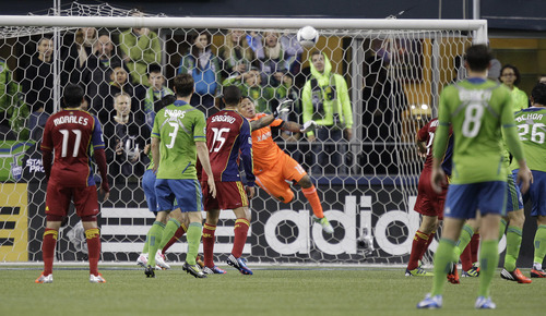 Real Salt Lake goalkeeper Nick Rimando, center, makes a save against the Seattle Sounders in the first half of an MLS soccer match on Friday, Nov. 2, 2012, in Seattle. (AP Photo/Ted S. Warren)