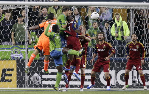 Real Salt Lake goalkeeper Nick Rimando, left, punches out the ball as Seattle Sounders' Jeff Parke, third from left, and Jhon Kennedy Hurtado, second from left, tangle with Real Salt Lake's Kwame Watson-Siriboe, center, and Nat Borchers (6) as Real Salt Lake's Ned Grabavoy, right, and Kyle Beckerman, second from right, look on in the first half of a MLS soccer playoff match on Friday, Nov. 2, 2012, in Seattle. (AP Photo/Ted S. Warren)