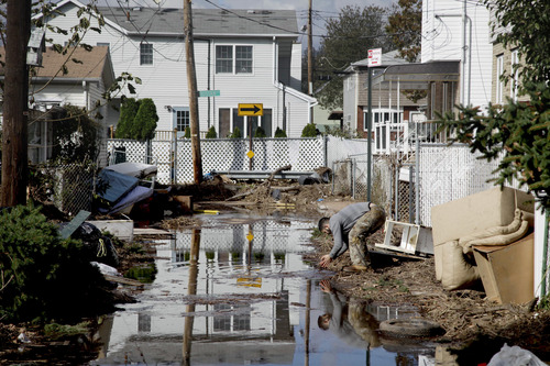 A man rinses his hands in flood water while cleaning out a house in a hard-hit neighbor hood in Staten Island, N.Y. Friday, Nov. 2, 2012.  Mayor Michael Bloomberg has come under fire for pressing ahead with the New York City Marathon. Some New Yorkers say holding the 26.2-mile race would be insensitive and divert police and other important resources when many are still suffering from Superstorm Sandy. The course runs from the Verrazano-Narrows Bridge on hard-hit Staten Island to Central Park, sending runners through all five boroughs. The course will not be changed, since there was little damage along the route.  (AP Photo/Seth Wenig)
