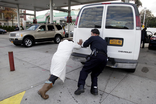 A police officer, right, helps Jason Bravo push an out-of-gas van into a gas station in the Brooklyn borough of New York, Friday, Nov. 2, 2012.   In parts of New York and New Jersey, drivers face another day of lining up for hours at gas stations struggling to stay supplied.  Superstorm Sandy damaged ports that accept fuel tankers and flooded underground equipment that sends fuel through pipelines. Without power, fuel terminals can't pump gasoline onto tanker trucks, and gas stations can't pump fuel into customers' cars.  (AP Photo/Seth Wenig)