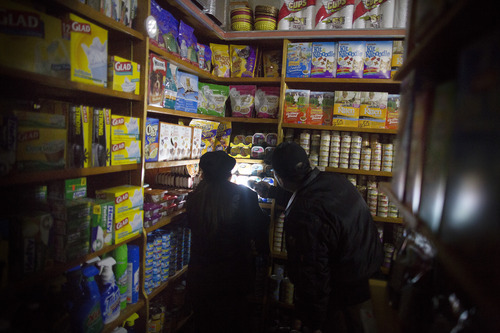 A shopkeeper assists a customer to buy dog food with a flashlight in a darkened Sheen Brothers corner store that remains without power due to Superstorm Sandy, Friday, Nov. 2, 2012, in New York. In Manhattan, where 226,000 buildings, homes and business remain without power, Consolidated Edison says they should have service restored by Saturday.  (AP Photo/ John Minchillo)