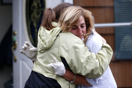 Kathleen Seemar, right, gets a hug from friend Ginny Baker while taking a break from cleaning out her flooded home to talk to friends as residents of Brick, N.J., cope following superstorm Sandy, Thursday, Nov. 1, 2012. Three days after Sandy slammed the mid-Atlantic and the Northeast, New York and New Jersey struggled to get back on their feet, the U.S. death toll climbed to more than 80, and more than 4.6 million homes and businesses were still without power. (AP Photo/Julio Cortez)