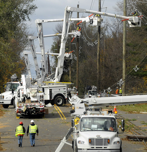 Visiting utility crews from the St. Louis-based Ameren Corp. restring power lines after replacing numerous downed and broken poles along Bull Run Road in Hopewell Township, N.J. on Saturday Nov. 3, 2012 in the aftermath of Hurricane Sandy. (AP Photo/The Trentonian, Jackie Schear)