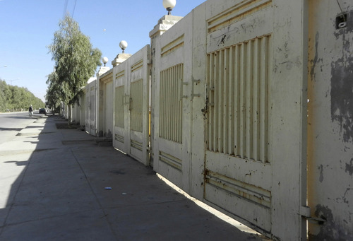 This Monday, Oct. 15, 2012 photo shows the closed gates of abandoned houses in the Ayno Maina district of Kandahar, Afghanistan. Only about 15,000 of the 40,000 lots have been sold, and 2,400 homes built and occupied, according to Mahmood Karzai, one of the development's main backers and a brother of President Hamid Karzai. (AP Photo/Allaudin Khan)
