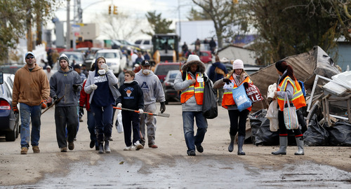 Volunteers walk toward homes to help residents clean up, Saturday, Nov. 3, 2012, in Staten Island, N.Y. A Superstorm Sandy relief fund is being created just for residents of the hard-hit New York City borough. Former Mayor Rudolph Giuliani and Borough President James Molinaro say the fund will help residents displaced from their homes. (AP Photo/Julio Cortez)