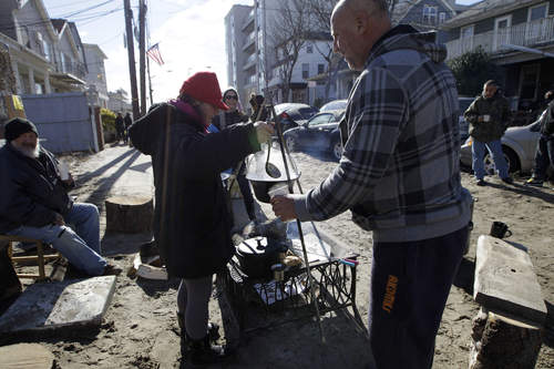 Kiva Kahl pour hot tea to neighbor Buddy Sammis,right, after she prepared it on an wood-stoked fire and cooking setup she and her fiance created in the street in front of their house on Beach 91st Street in the Rockaways, Saturday, Nov. 3, 2012 in New York. More New Yorkers awoke Saturday to power being restored for the first time since Superstorm Sandy pummeled the region, but patience wore thin among those in the region who have been without power for most of the week. (AP Photo/Kathy Willens)