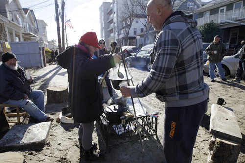 Kiva Kahl pours hot tea for neighbor Buddy Sammis,right, after she prepared it on a wood-stoked fire and cooking setup she and her fiance created in the street in front of their house on Beach 91st Street in the Rockaways, Saturday, Nov. 3, 2012, in New York. More New Yorkers awoke Saturday to power being restored for the first time since Superstorm Sandy pummeled the region, but patience wore thin among those in the region who have been without power for most of the week. (AP Photo/Kathy Willens)