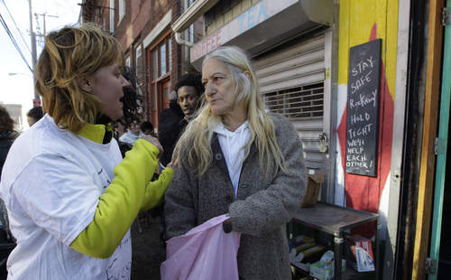 Rockaways resident Catherine Yeager, left, talks with fellow resident Linda Allen, who has been living without heat, power, gas, or fresh food all week, after Yeager provided free bagels, a free flashlight and batteries from Yeager, who together with three neighborhood friends set up a donation point outside a small juice bar along a road near the Atlantic Ocean, Saturday, Nov. 3, 2012, in New York. The Rockaways was hard hit by Superstorm Sandy earlier in the week and still has no power. (AP Photo/Kathy Willens)