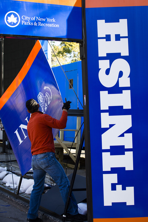 A worker dismantles sponsorship signs at the Central Park finish line for the now-canceled New York Marathon, Saturday, Nov. 3, 2012, in New York. Mayor Michael Bloomberg canceled the race after mounting criticism that this was not the time for a race, as the city continues to recover from Superstorm Sandy. (AP Photo/ John Minchillo)