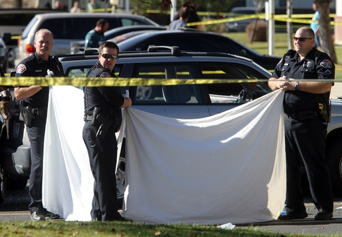 Rick Egan  | The Salt Lake Tribune Officers block the view of the victim of a fatal shooting at the Lexington Park apartments in West Valley City, after a fatal shooting at the complex, Friday, November 2, 2012.