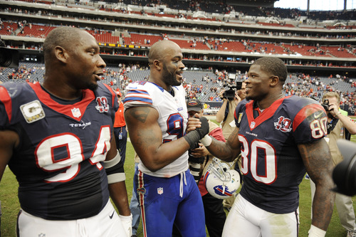 Buffalo Bills defensive end and former Houston Texan Mario Williams, center, meets with Texans' Antonio Smith (94) and Andre Johnson (80) after an NFL football game on Sunday, Nov. 4, 2012, in Houston. The Texans won 21-9. (AP Photo/Dave Einsel)