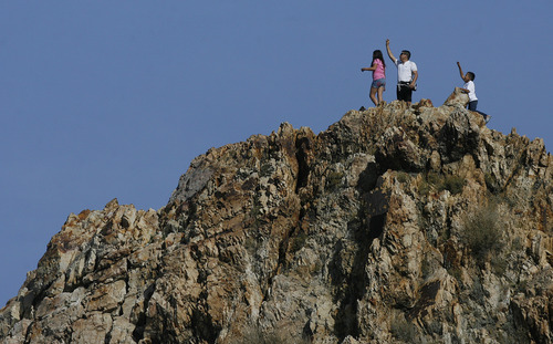 Scott Sommerdorf  |  The Salt Lake Tribune               A family seems to wave to Salt Lake City after they crested the climb onto the top of Pete's Rock just off Wasatch Blvd. in Salt Lake City, Sunday, November 4, 2012.