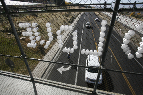 "Scott Sommerdorf  |  The Salt Lake Tribune               Cups in the chain link fence of the Oakview Drive overcrossing over Wasatch Blvd spell out ""LIVE AND LOVE"" as car and bike traffic pass beneath, Sunday, November 4, 2012."