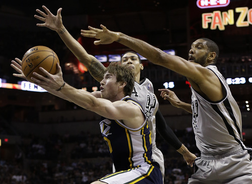 Utah Jazz' Gordon Hayward is defended by San Antonio Spurs' Tim Duncan, right, and Danny Green, center, as he drives to the basket during the first quarter of an NBA basketball game, Saturday, Nov. 3, 2012, in San Antonio. San Antonio won 86-84. (AP Photo/Eric Gay)