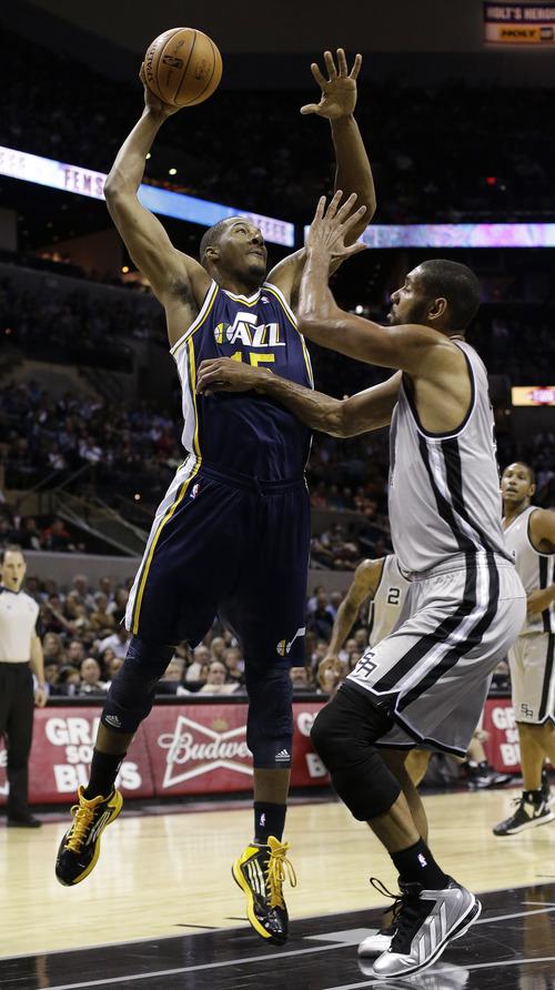 Utah Jazz' Derrick Favors, left, shoots over San Antonio Spurs' Tim Duncan, right, during the first quarter of an NBA basketball game, Saturday, Nov. 3, 2012, in San Antonio. San Antonio won 86-84. (AP Photo/Eric Gay)