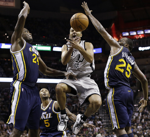 San Antonio Spurs' Tony Parker, center, of France, loses control of the ball as he is defended by Utah Jazz' Paul Millsap (24), Mo Williams (5) and Al Jefferson (25) during the third quarter of an NBA basketball game, Saturday, Nov. 3, 2012, in San Antonio. (AP Photo/Eric Gay)