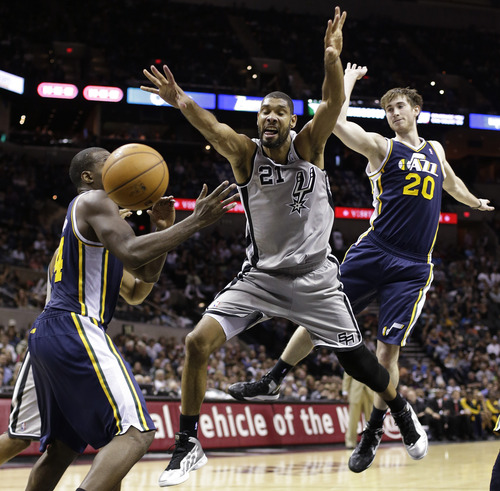 San Antonio Spurs' Tim Duncan (21) loses control of the ball as he is defended by Utah Jazz' Paul Millsap, left, and Gordon Hayward (20) during the fourth quarter of an NBA basketball game, Saturday, Nov. 3, 2012, in San Antonio. (AP Photo/Eric Gay)