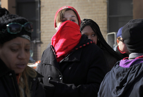 Nicole Vasquez uses a scarf to keep warm while waiting for food at an American Red Cross station in the Coney Island section of Brooklyn, Monday, Nov. 5, 2012 in New York. The region is still cleaning up a week after Superstorm Sandy. (AP Photo/Mark Lennihan)