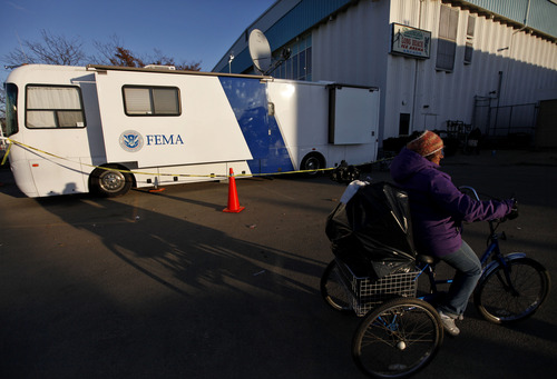 Jason DeCrow  |  The Associated Press A woman pedals her loaded tricycle past a Federal Emergency Management Agency trailer after receiving relief supplies from a clothing and food distribution center, Monday, Nov. 5, 2012, in Long Beach, N.Y.