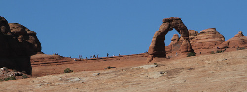 Francisco Kjolseth  |  The Salt Lake Tribune Visitors get a close up view of Delicate Arch at Arches National Park in southern Utah recently. The park's infrastructure was created based on an annual average visitation of 75,000. The park surpassed 1 million visitors in 2010 and is steadily climbing. Officials at Arches are considering options to reduce the number of cars in the park and a shuttle system is one option. However, it would be expensive and, if visitation numbers keep going up, it could soon be obsolete.