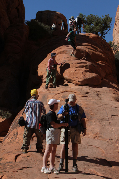 Francisco Kjolseth  |  The Salt Lake Tribune A line of visitors crowds the hike along the Devils Garden loop, a popular trail that draws people from all over the world. The infrastructure of Arches National Park was created based on an annual average visitation of 75,000. The park surpassed 1 million visitors in 2010 and is steadily climbing. Officials at Arches are considering options to reduce the number of cars in the park and a shuttle system is one option. However, it would be expensive and, if visitation numbers keep going up, it could soon be obsolete.