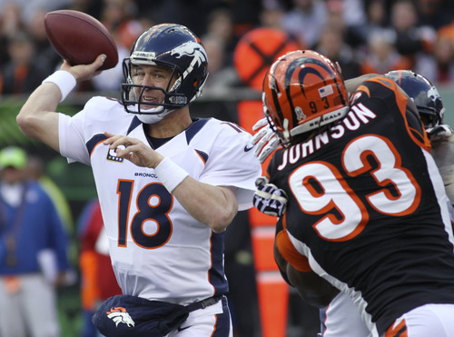 Denver Broncos quarterback Peyton Manning (18) passes under pressure from Cincinnati Bengals defensive end Michael Johnson (93) during the first half of an NFL football game, Sunday, Nov. 4, 2012, in Cincinnati. (AP Photo/Tom Uhlman)