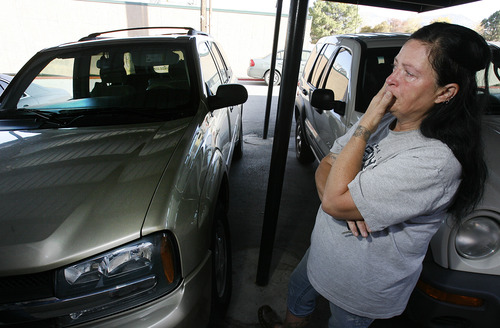 Scott Sommerdorf  |  The Salt Lake Tribune               LoEne Lookebill tears up when she describes the issues she's had in trying to work with Holly Oil to get her vehicle repaired after it was covered in oil by a recent tank explosion. Her SUV, at left, looks clean to the naked eye, but, she explains oil remains in crevices, and oil leaks from everywhere when it rains. She says her insurance wants to total out the car because it is a hazardous liability. The problem is Holly Oil won't pay for what the car is worth for her to get it fixed or to pay off the payments on the car.