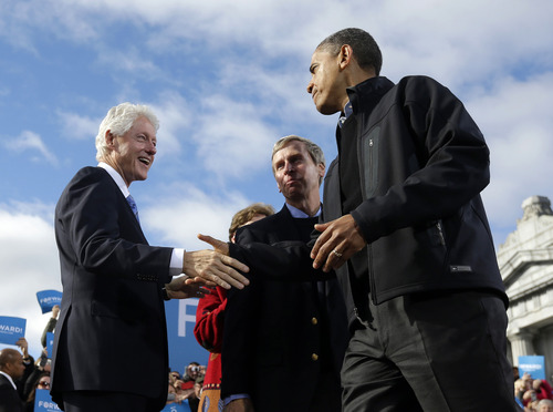 President Barack Obama, right, shakes hands with former President Bill Clinton, left, as New Hampshire Gov. John Lynch, center, watches on stage together during a campaign event at Capitol Square, Sunday, Nov. 4, 2012, in Concord, N.H.  (AP Photo/Pablo Martinez Monsivais)