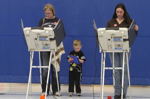 Rick Egan  | The Salt Lake Tribune   Amy Deming (left) votes as her son Max, 4, concentrates on his V-Reader, and Wendy Watt (right) votes at Pony Express Elementary School in Eagle Mountain, Tuesday, Nov. 6, 2012.