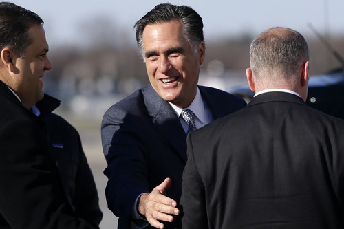 Republican presidential candidate, former Massachusetts Gov. Mitt Romney smiles as he speaks to a U.S. Secret Service agent before boarding his plane in Bedford Mass., for Cleveland, Ohio, Tuesday, Nov. 6, 2012. (AP Photo/Charles Dharapak)