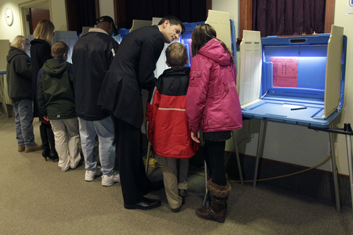 Republican vice presidential candidate, Rep. Paul Ryan, R-Wis., votes with his children Sam and Liza, as his wife Janna, second from left, votes with Charlie, at the Hedberg Public Library in Janesville, Wis., Tuesday, Nov. 6, 2012.  (AP Photo/Mary Altaffer)