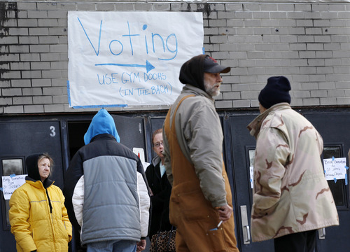People, many displaced from the Jersey Shore by Superstorm Sandy, stand outside the shelter where they are staying at Toms River East High School Tuesday, Nov. 6, 2012, in Toms River, N.J. The school is also a polling station for elections Tuesday. (AP Photo/Mel Evans)