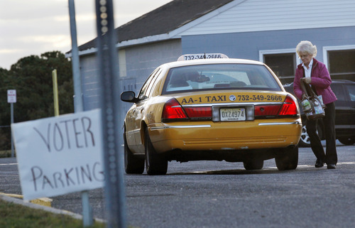 A woman arrives by taxi to vote at a polling place at Toms River East High School to vote early election day Tuesday, Nov. 6, 2012, in Toms River, N.J.  (AP Photo/Mel Evans)