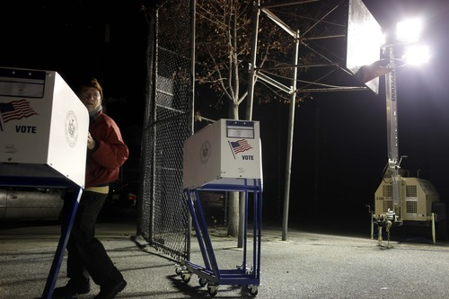 Under the lights of a generator, poll worker John DeSilva moves voting booths into a tent serving as a polling site in the Midland Beach section of Staten Island, New York, on Election Day, Tuesday, Nov. 6, 2012.  The original polling site, a school, was damaged by Superstorm Sandy. (AP Photo/Seth Wenig)