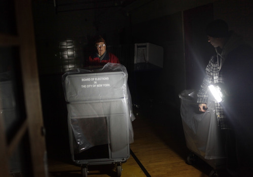 Working by flashlight, poll worker John DeSilva, left, and school custodian Rob Digiaimo move voting machines from the original polling site to a tent site in the Midland Beach section of Staten Island, New York, on Election Day, Tuesday, Nov. 6, 2012. The original polling site was damaged by Superstorm Sandy. (AP Photo/Seth Wenig)