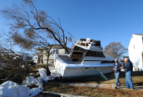 A boat owner, right, talks to a representative from BoatsUS to recover his boat that landed on the front lawn between two homes on Grant Street swept away from a nearby marina from the powerful storms of Hurricane Sandy on Monday, Nov. 5, 2012, in Freeport, N.Y. (AP Photo/Kathy Kmonicek)