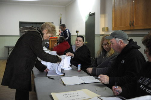 Patricia Hiller of Lido Beach, N.Y., left, signs in to vote at Bishop Molloy Recreational Center on Tuesday, Nov. 6, 2012, in Point Lookout , N.Y., one of several voting locations that were created as a result of Superstorm Sandy. (AP Photo/Kathy Kmonicek)