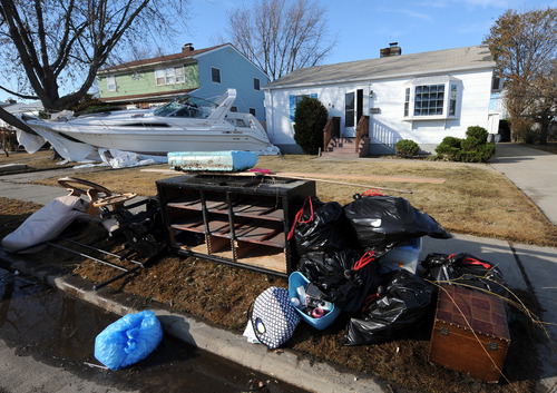 One of several boats that were swept away from a nearby marina during Hurricane Sandy on the front lawn of a home on Robert Street on Monday, Nov 5, 2012, in Freeport, N.Y. Throughout the neighborhood, the streets were also filled with possessions ruined by flooding. (AP Photo/Kathy Kmonicek)