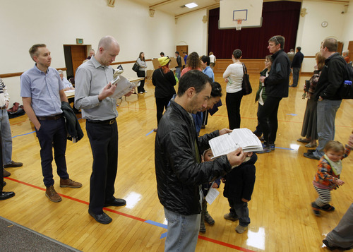 Al Hartmann  |  The Salt Lake Tribune People look over voting guides Tuesday morning, Nov. 6 as they wait to vote at the Salt Lake Ensign LDS Church at 109 G St. in Salt Lake City, which houses precincts SLC033 and SLC039.