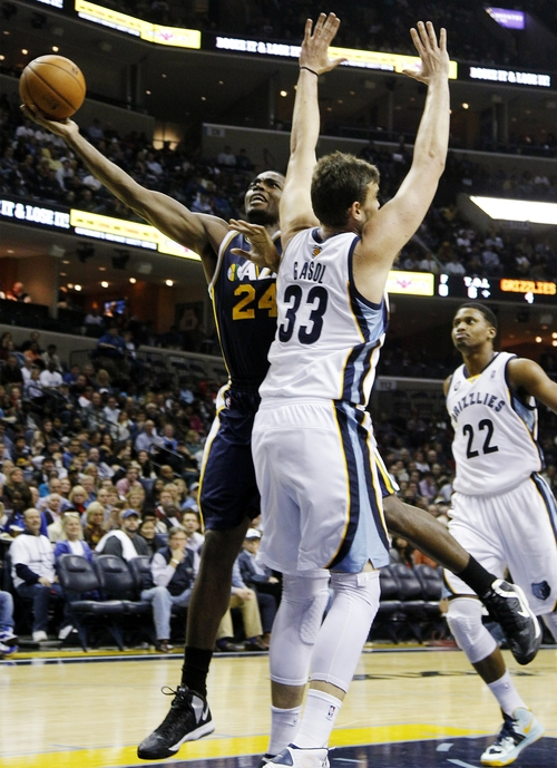 Utah Jazz forward Paul Millsap (24) goes to the basket against Memphis Grizzlies center Marc Gasol (33), of Spain, and forward Rudy Gay (22) in the first half of an NBA basketball game, Monday, Nov. 5, 2012, in Memphis, Tenn. (AP Photo/Lance Murphey)
