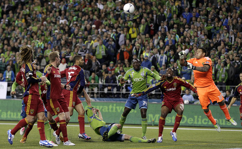 Real Salt Lake goalkeeper Nick Rimando, right, punches out a ball as Seattle Sounders' Jhon Kennedy Hurtado (34) and Real Salt Lake's Jamison Olave, second from right, battle for position in the second half of a MLS Western Conference semifinal soccer match, Friday, Nov. 2, 2012, in Seattle. The match, the first of a two-match aggregate-score game, ended with a score of 0-0. (AP Photo/Ted S. Warren)