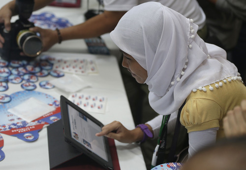 A Muslim student votes in the mock U.S. election at a shopping mall at suburban Quezon city, northeast of Manila, Philippines Wednesday, Nov. 7, 2012. Filipinos participated in a mock U.S. election between President Brack Obama and Republican Mitt Romney which was organized by the US Embassy in Manila. (AP Photo/Bullit Marquez)