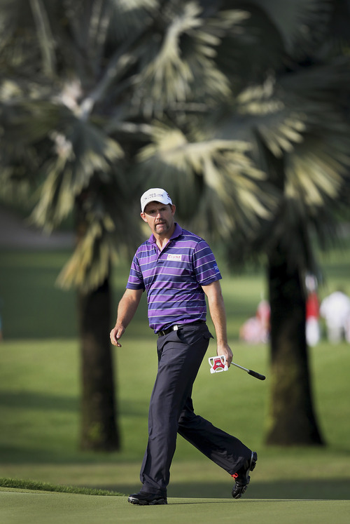 Padraig Harrington of Ireland watches his shot on the 12th hole during the first round of the Singapore Open golf tournament at the Serapong Course at Sentosa Golf Club in Singapore on Thursday, Nov. 8, 2012. (AP Photo/Wong Maye-E)