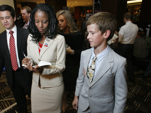 Scott Sommerdorf  |  The Salt Lake Tribune               4th Congressional candidate Mia Love signs an autograph and writes an additional message for young supporter Jessie Harsh at the GOP headquarters at the Hilton Hotel in Salt Lake City, Tuesday, November 6, 2012